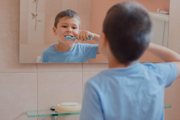 Счастливый ребенок или ребенок, чистить зубы в ванной комнате.