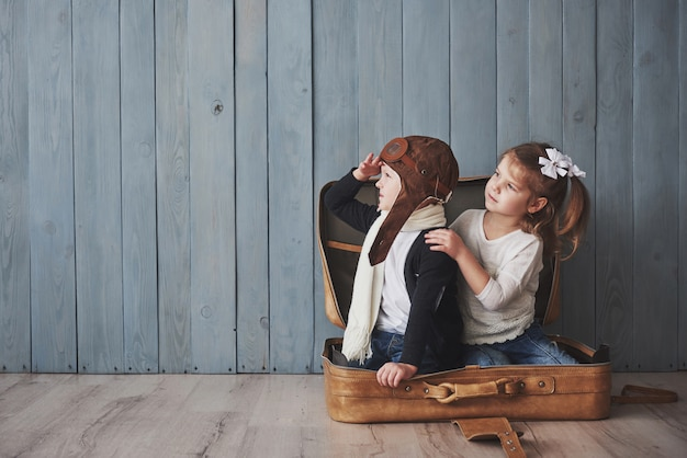 Happy kid in pilot hat and little girl playing with old suitcase. childhood. fantasy, imagination. travel