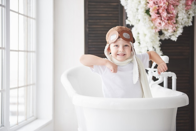 Happy kid in pilot hat playing in bathroom. childhood. fantasy, imagination.