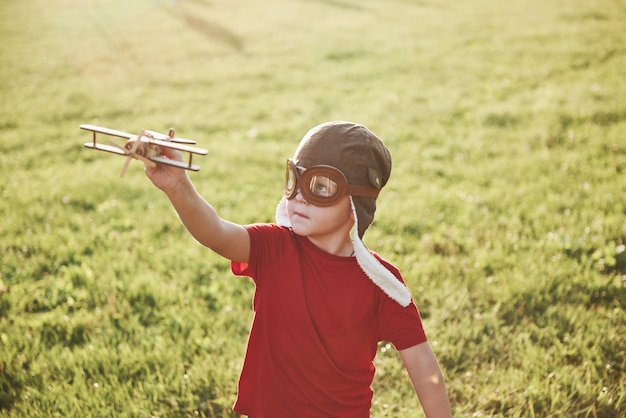 Happy kid in pilot helmet playing with a wooden toy airplane and dreaming of becoming flying