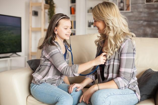 Счастливый ребенок играет роль врача, чтобы проверить ее сердце матери с помощью стетоскопа.