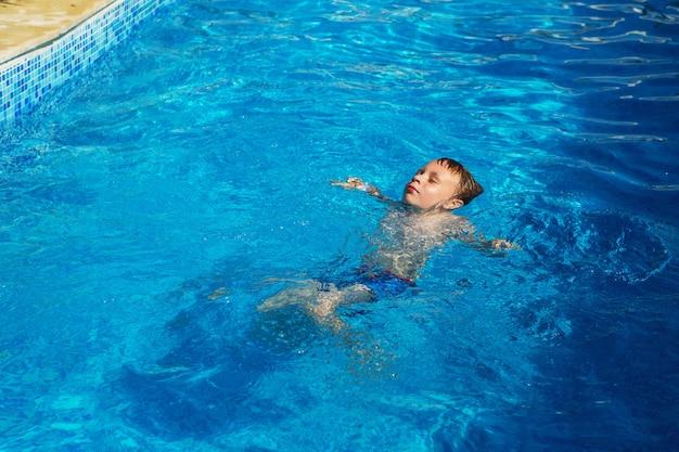海のトロピカルリゾートのプールの青い水で遊ぶ幸せな子供