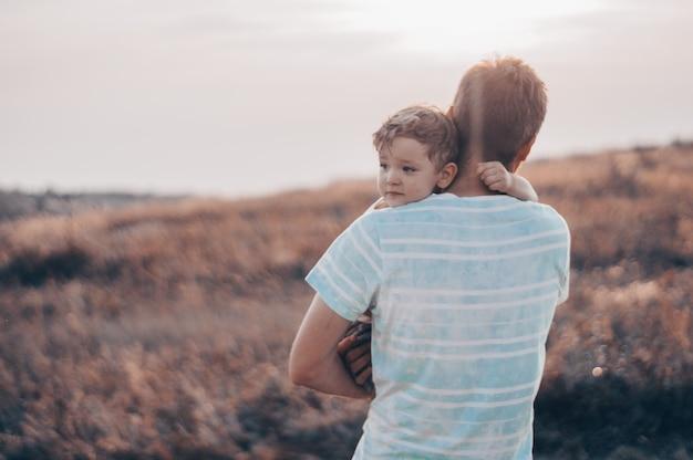 Счастливый ребенок играет с отцом. папа и сын на природе. отец несет ребенка на спине. счастливая семья в летнем поле.