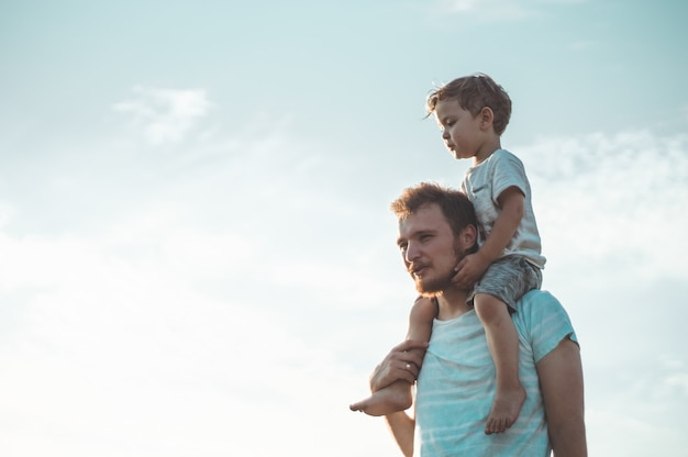 Happy kid playing with father. dad and son outdoors. father carrying child on his back. happy family in summer field.