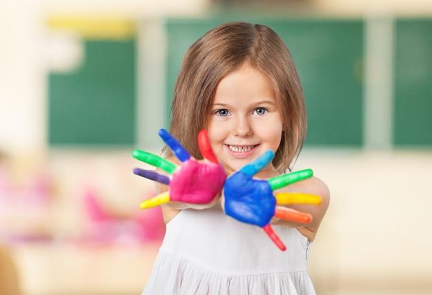 彼の指で絵の具で遊んで幸せな子供。