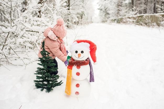 눈사람을 가지고 노는 행복 한 꼬마. 겨울 야외에서 산책에 재미있는 어린 소녀