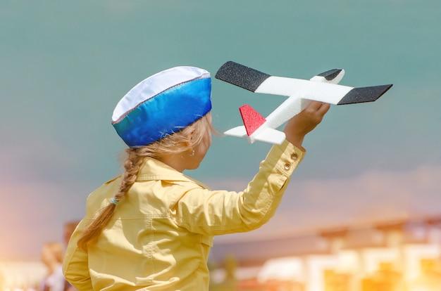 푸른 여름 하늘 배경에서 장난감 비행기를 가지고 노는 행복한 아이.