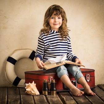 屋内でおもちゃの帆船で遊んで幸せな子供。旅行と冒険のコンセプト