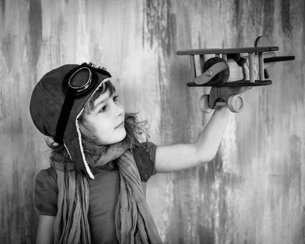 실내에서 장난감 나무 비행기를 가지고 노는 행복한 아이. 흑백 사진
