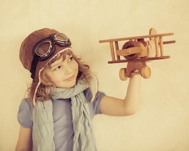 실내에서 장난감 나무 비행기를 가지고 노는 행복한 아이