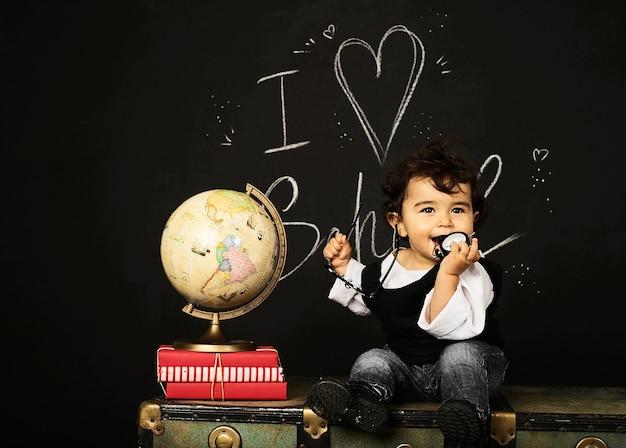 幸せな子供幼稚園の男の子、書籍、地球儀、時計、学校の近く、黒板、胸に座る