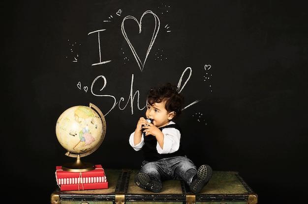 Happy kid preschool boy with books, globe and clock near school board blackboard sitting on a chest