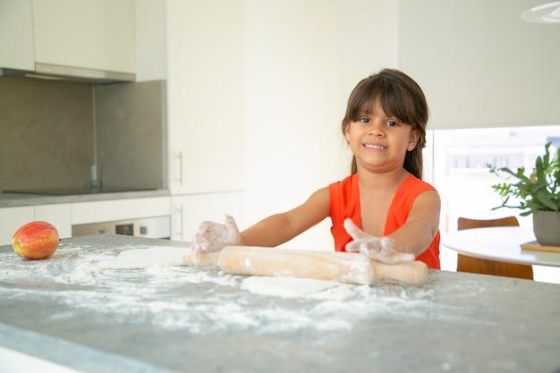 Bambino felice che rotola la pasta al tavolo della cucina da sola. ragazza con farina sulle braccia che cuociono il pane o la torta. colpo medio. concetto di cucina familiare