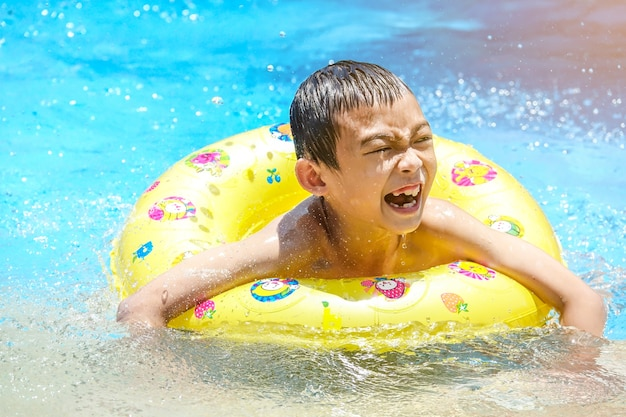 Happy kid on safety ring in swimming pool