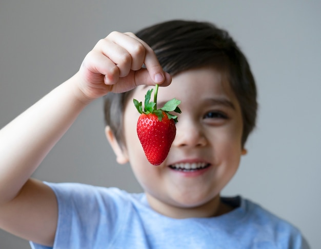 A happy kid showing fresh strawberries