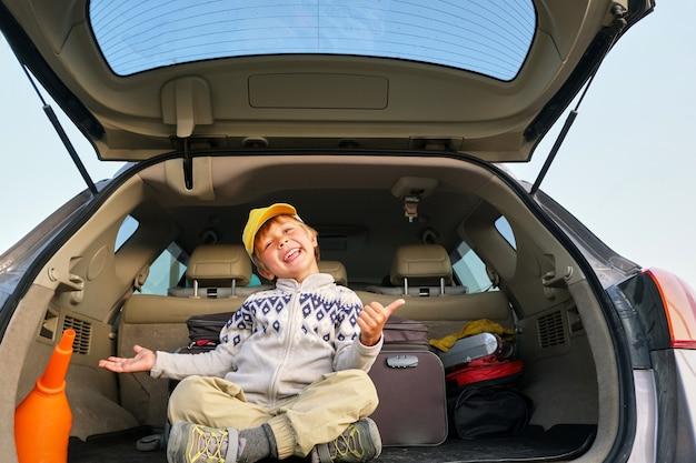여행을 위해 자동차 트렁크에 앉아 있는 행복한 아이