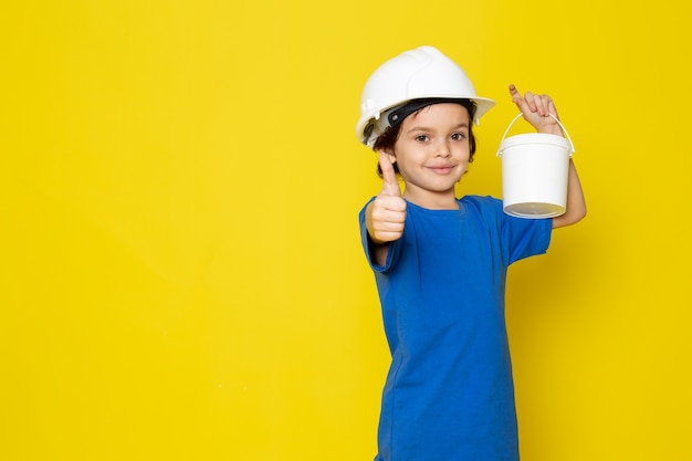 Happy kid smiling adorable cute holding paints in blue t-shirt on yellow wall