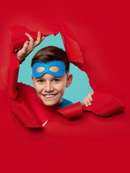 Happy kid in superhero mask looking through hole in paper