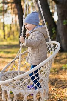 Счастливый малыш качается в подвесном кресле в лесу осенью