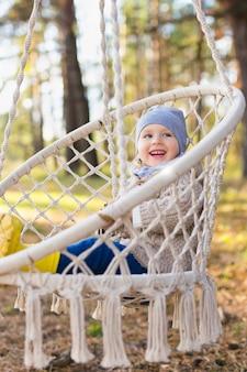 Счастливый малыш качается в подвесном кресле в лесу