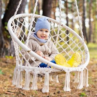 Счастливый малыш качается в подвесном кресле на открытом воздухе