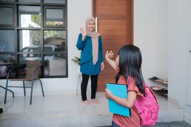 Happy kid waves goodbye to mother before going to school in the morning