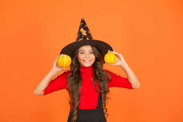 Happy kid in witch hat costume to halloween with small yellow pumpkin, halloween food.