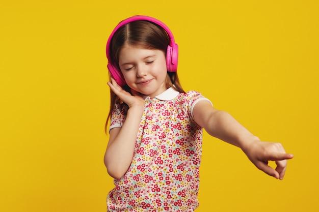 Счастливый ребенок с розовыми наушниками, слушает музыку и танцует с закрытыми глазами