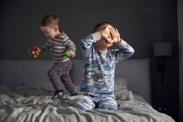 행복한 아이들이 아늑한 침실에서 놀고 있습니다.