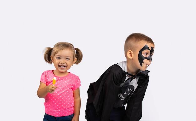 Счастливые дети на вечеринке в честь хэллоуина со счастливой улыбкой и леденцами. милый мальчик и девочка на белой стене.