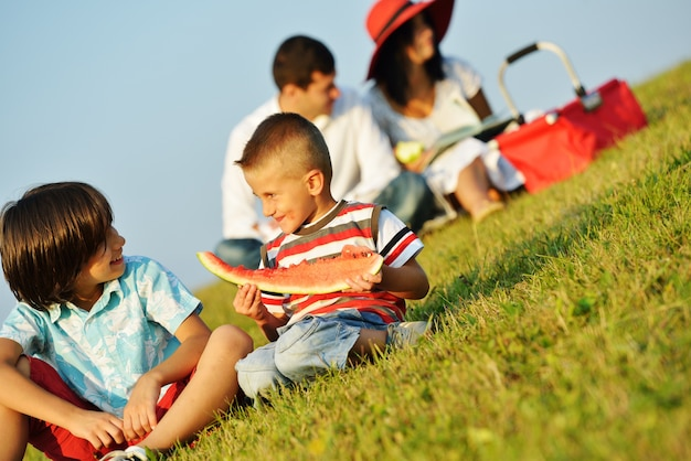 Happy kids on beautiful summer meadow having happy time making picnic