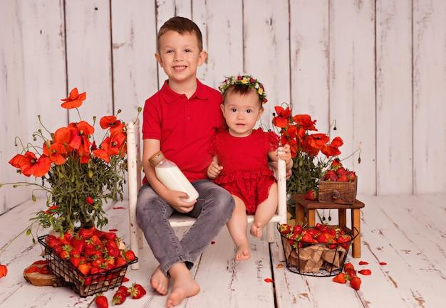 幸せな子供の男の子と女の子は、牛乳とイチゴを食べます。花瓶にケシの花束。