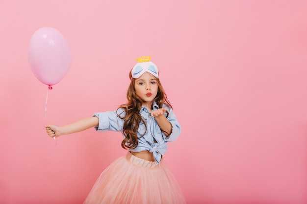 Happy kids carnival of little amazing girl with long brunette hair holding balloon and sending kiss to camera isolated on pink background. wearing tulle skirt, princess cute mask on head
