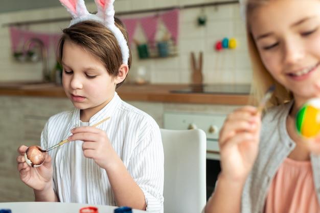 幸せな子供のイースターエッグを着色、イースターバスケットの準備