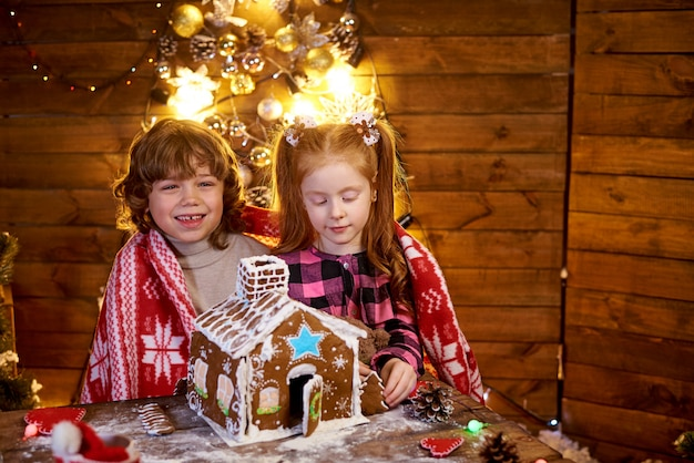 Happy kids create christmas gingerbread house