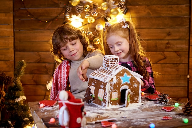 Happy kids create christmas gingerbread.