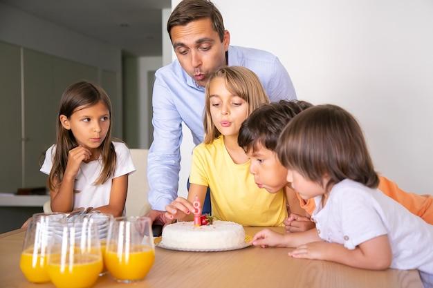 Bambini felici e papà che spegne la candela sulla torta e che esprime desiderio. bella ragazza bionda che festeggia il suo compleanno con gli amici. bambini felici in piedi vicino al tavolo. infanzia, celebrazione e concetto di vacanza