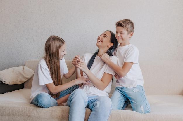 幸せな子供たちの娘と息子、ソファで遊んだり、お母さんと遊んだり。