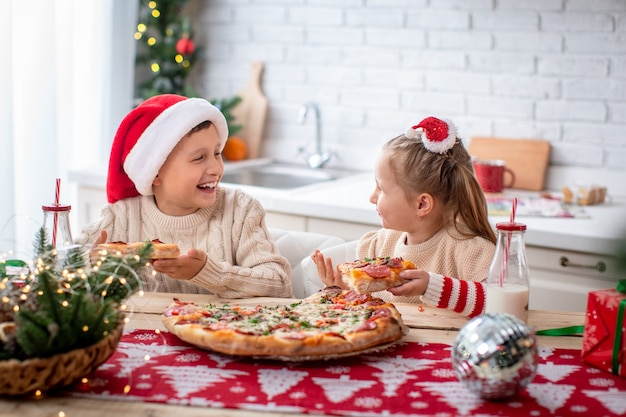Happy kids eating pizza in the kitchen decorated for christmas