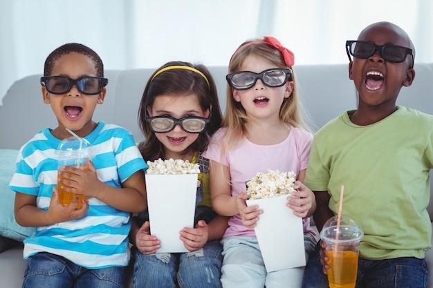 Счастливые дети наслаждаются попкорном и напитками, сидя