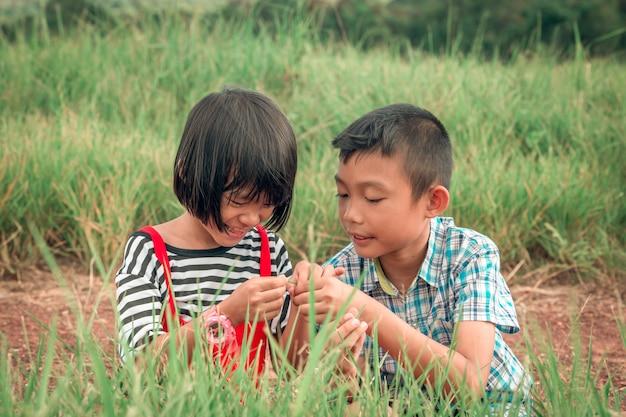 幸せな子供の家族の兄と妹の丘の上の芝生のフィールドで遊んで