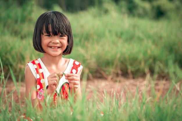 丘の上の芝生のフィールド、背景にぼやけている緑の牧草地で笑っている幸せな子供の女の子