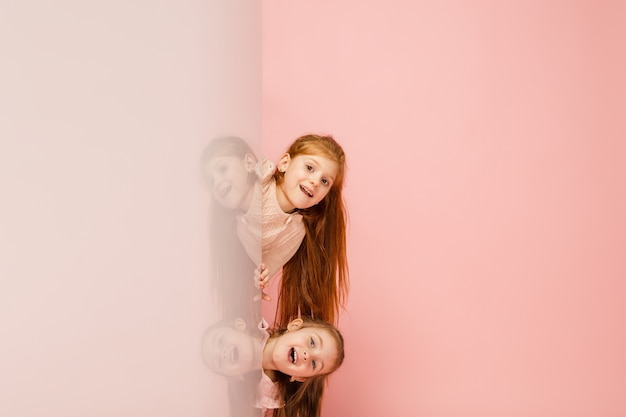 Happy kids, girls isolated on coral pink