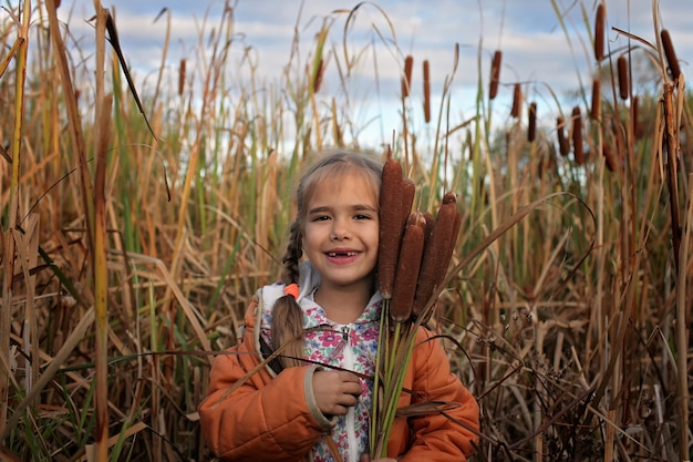 A happy kids having fun in the field of cattails, ecology concept