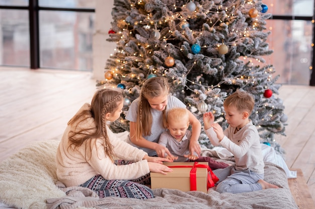 Happy kids having fun and opening presents near christmas tree.