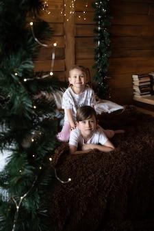 クリスマスツリーのパジャマの近くでクリスマスの朝に遊ぶパジャマの幸せな子供たち