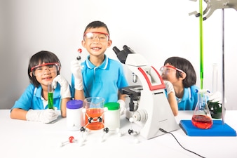 Happy kids in science laboratory on gray background
