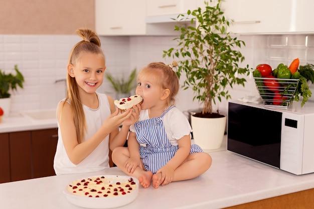 부엌에서 행복한 아이들. 자매는 맛있는 치즈 케이크를 먹는다
