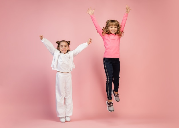 Happy kids isolated on coral pink studio wall