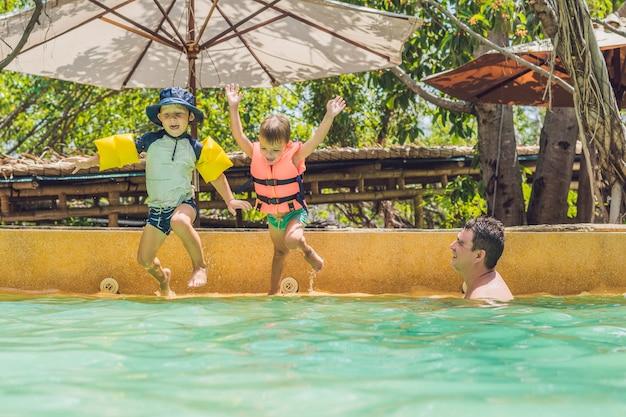 행복한 아이들이 밝고 화창한 날에 연못으로 뛰어 들어 많은 스프레이를 올리십시오.